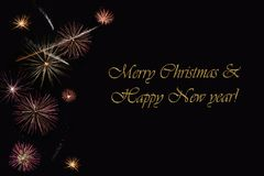 Фейерверки на темной ` предпосылки и ` текста с Рождеством Христовым & счастливом Нового Года Стоковые Изображения RF