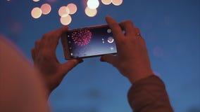 Фейерверки стрельбы девушки на смартфоне Женщина снимает салют по телефону Создайте видео на ее смартфоне r видеоматериал