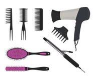 Фен для волос, завивая утюг и разные виды щеток волос на белой предпосылке Стоковое Фото
