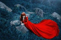 Ферзь в роскошном, дорогом, красном платье, с длинным поездом лежит на чащах плюща Рыжеволосая девушка в золоте стоковые изображения rf