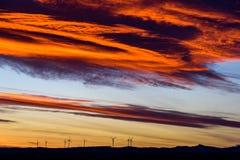 Ферма ветротурбин в расстоянии на красивом заходе солнца красного цвета, апельсина и сини Стоковые Изображения