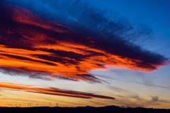 Ферма ветротурбин в расстоянии на красивом заходе солнца красного цвета, апельсина и сини Стоковая Фотография RF