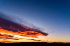 Ферма ветротурбин в расстоянии на красивом заходе солнца красного цвета, апельсина и сини Стоковое Изображение