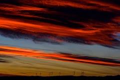 Ферма ветротурбин в расстоянии на красивом заходе солнца красного цвета, апельсина и сини Стоковые Изображения RF