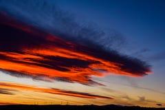 Ферма ветротурбин в расстоянии на красивом заходе солнца красного цвета, апельсина и сини Стоковое Изображение RF