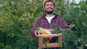 Фермеры выходят на рынок, радостный человек в соломенной шляпе держат деревянную клеть с органическими свежими овощами для продаж видеоматериал
