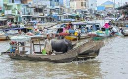 Фермеры грузя торговлю буйвола в плавая рынке Стоковое Изображение