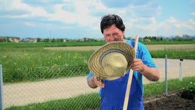 Фермер в одеждах деятельности кладет шляпу сена на его голову и продолжает работать видеоматериал
