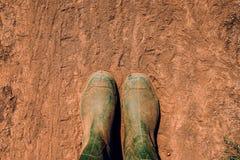 Фермер в резиновых ботинках стоя на грязной улице стоковое фото rf