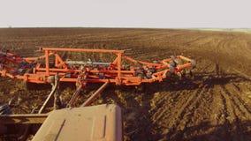Фермер в тракторе вспахивает почву земледелия движения steadicam России земная подготавливая земля с рыхлителем seedbed как видеоматериал