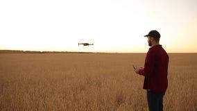Фермер держит удаленный регулятор с его руками пока quadcopter летает на предпосылку Трутень спускает за акции видеоматериалы