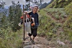 Фермер женщины возвращает от работы на местах с сапкой и хомутом Стоковое фото RF