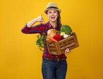 Фермер женщины с коробкой показывать овощей вызывает меня жестом Стоковая Фотография
