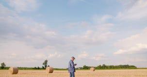 Фермер используя цифровой планшет пока рассматривающ поле сток-видео