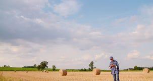 Фермер используя цифровой планшет пока рассматривающ поле акции видеоматериалы