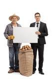 Фермер и бизнесмен держа пустой картон подписывают Стоковые Фото