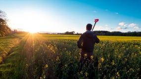 Фермер смотря поле цветка рапса Стоковое Изображение RF
