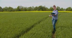 Фермер с заводами доски сзажимом для бумаги рассматривая во время вет видеоматериал