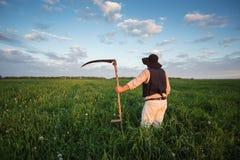 Фермер с косой на зеленом поле стоковая фотография rf