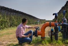 Фермер с таблеткой около полива пускает по трубам в яблоневом саде стоковые фото