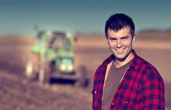 Фермер с трактором на поле Стоковые Изображения