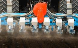 Фермер с трактором осеменяя урожаи сои на аграрном поле стоковые фотографии rf