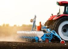 Фермер с трактором осеменяя урожаи сои на аграрном поле стоковые изображения
