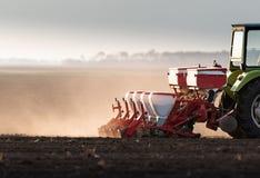 Фермер с трактором осеменяя урожаи сои на аграрном поле стоковое фото rf