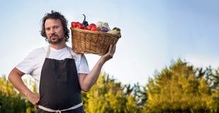 Фермер с экологическим сбором овощей в корзине близко стоковое фото