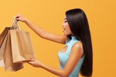 Фестиваль двойника 11 ходя по магазинам Счастливая азиатская женщина на покупках держа сумку и телефон изолированными на голубой  Стоковые Изображения