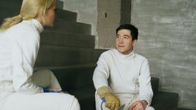 2 фехтовальщика человек и женщина деля опыт во время пролома ограждать спичку внутри помещения
