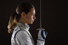 Фехтовальщик молодой женщины держа шпагу перед ей Стоковое фото RF