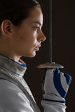 Фехтовальщик молодой женщины держа шпагу перед ей Стоковые Фотографии RF