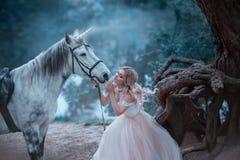 Фея в нежном винтажном платье обнимает единорога Фантастическая волшебная, излучающая лошадь Блондинка реки и леса предпосылки стоковое фото