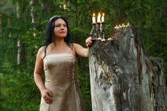 Фея леса в светлом платье на большом пне с подсвечником со свечами стоковая фотография rf