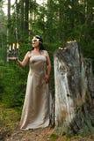 Фея леса в светлом платье с маской на ее стороне в лесе с подсвечником с свечами общий план стоковые изображения rf