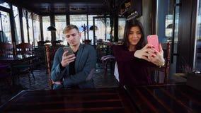 Физик с smartwatch в наличии в кафе при коллега принимая selfies используя друга smartphone ждать сток-видео