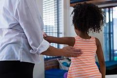 Физиотерапевт давая задний массаж к пациенту девушки в клинике Стоковое фото RF