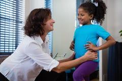 Физиотерапевт давая задний массаж к пациенту девушки в клинике Стоковое Изображение