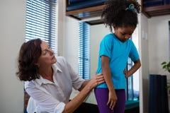 Физиотерапевт давая задний массаж к пациенту девушки Стоковые Фото