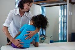 Физиотерапевт давая задний массаж к пациенту девушки Стоковое Изображение RF