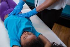 Физиотерапевт давая массаж брюшка к пациенту девушки Стоковые Изображения RF