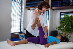 Физиотерапевт давая массаж ноги к пациенту девушки Стоковая Фотография