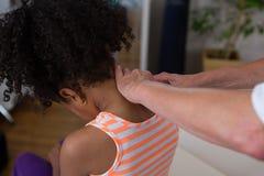 Физиотерапевт давая массаж шеи к пациенту девушки Стоковые Фотографии RF