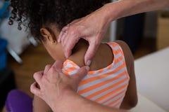 Физиотерапевт давая массаж шеи к пациенту девушки Стоковые Изображения RF