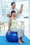 Физиотерапевт давая физиотерапию к беременной женщине Стоковая Фотография
