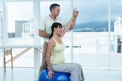 Физиотерапевт давая физиотерапию к беременной женщине Стоковые Изображения