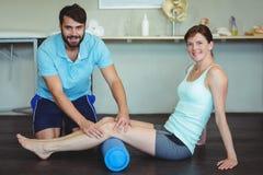 Физиотерапевт делая терапию ноги к женщине используя крен пены Стоковое Изображение