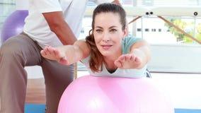 Физиотерапевт используя шарик тренировки с пациентом видеоматериал
