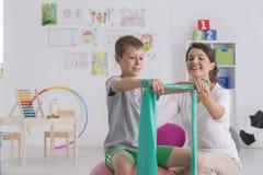 Физиотерапевт и мальчик сидя на шарике спортзала Стоковое Изображение RF